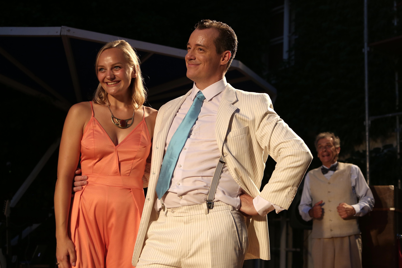 Anna Zöch Bühne strahelnd mit Partner im orangenen Jumpsuit